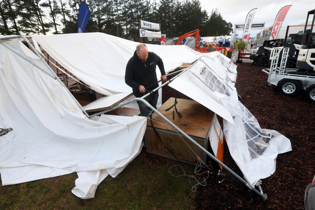 Kris Fannin of Cambridge fixes up a tent on the Contractors Federation site blown down by strong winds over night at National Fieldays at Mystery Creek.