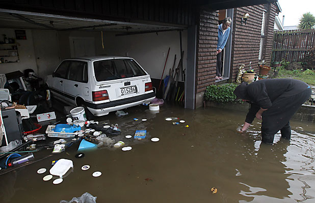 HELPING HAND: Bernadette Thomas surveys the scene in her flooded garage on Whitefield St as neighbour Harley Robb helps to pump water away.