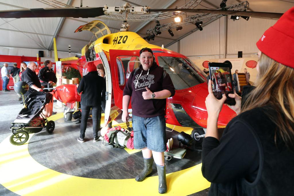 Thumbs up: Zac Gillespie of Inglewood gets his pic taken by Ebony de Thierry in front of a Westpac Rescue Helicopter at the National Agricultural Fieldays at Mystery Creek.