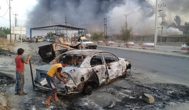 WAR ZONE: Children stand next to a burnt vehicle during clashes between Iraqi security forces and al Qaeda-linked Islamic State in Iraq and the Levant (ISIL) in the northern Iraq city of Mosul.