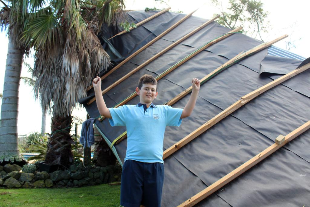 Davies, 11, in front of the roof of his home which blew off in high winds at Wainui in the Rodney District.