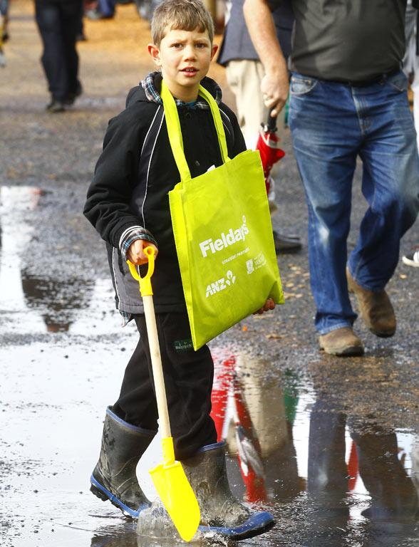 Tyler Wetere, 8, complete with goodies bag around this neck, negotiates a walkway at the 2014 National Fieldays at Mystery Creek.