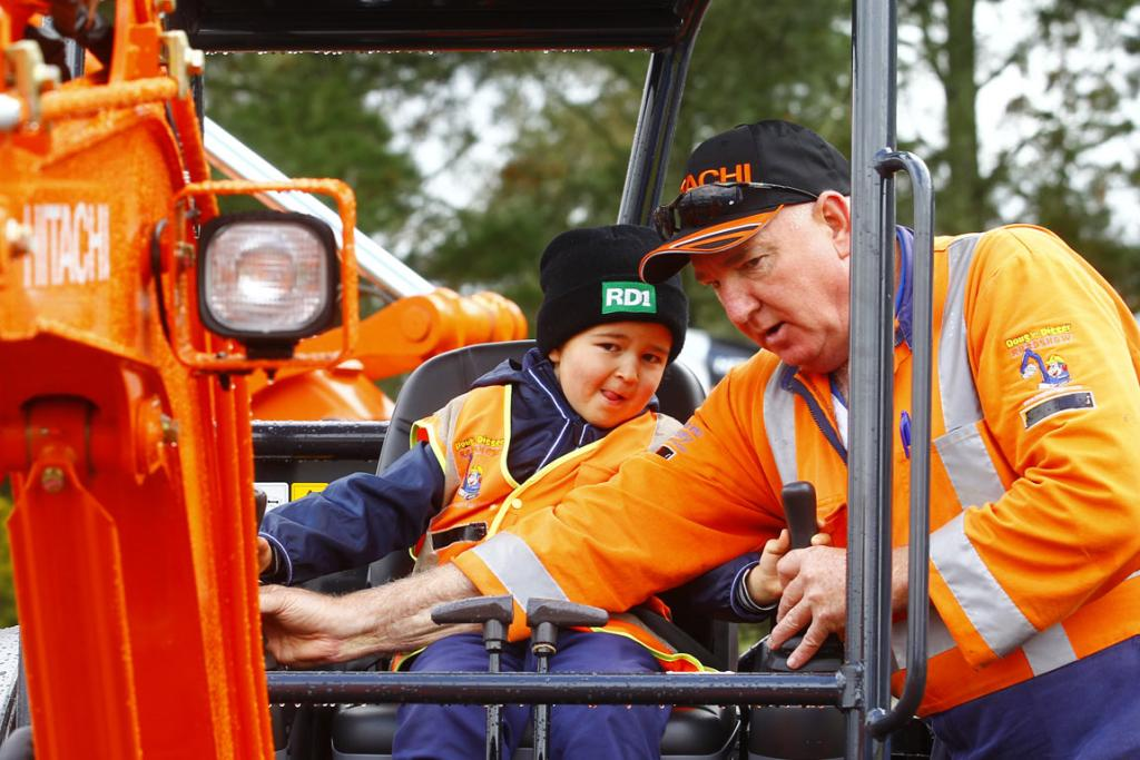 Mark Birks, 5, gets some digger driving advice from Alistair McIntyre at the 2014 National Fieldays at Mystery Creek.