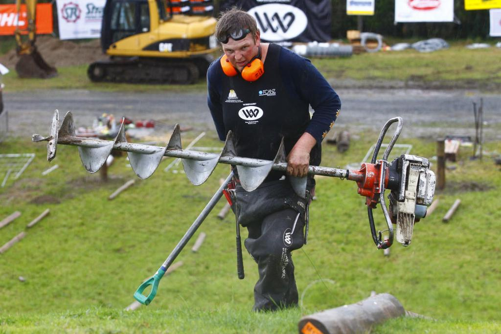 Mark Lambert carries a post hole borer in the fencing competition at the 2014 National Fieldays at Mystery Creek.