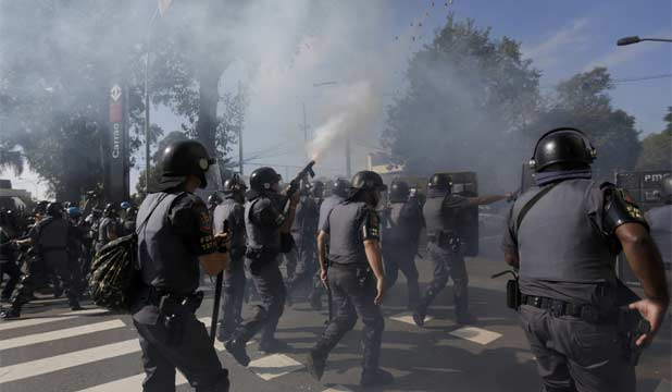 CLASHES: Police fire tear gas into the air to disperse a protest near Corinthians Arena in eastern Sao Paulo ahead of the opening match of the football World Cup.