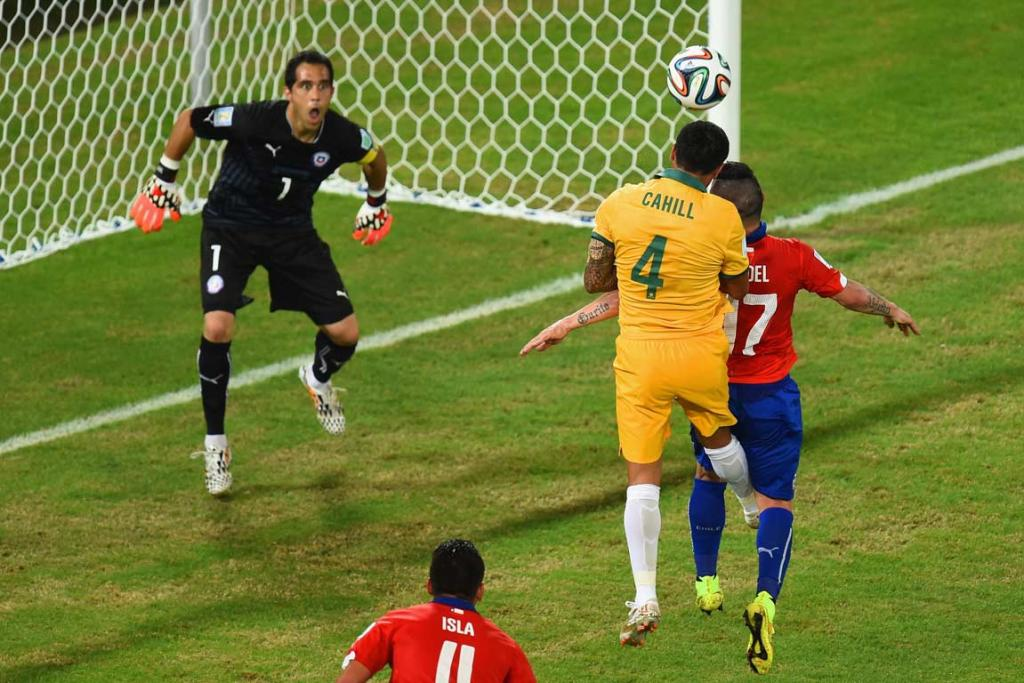 Tim Cahill leaps above Gary Medel to head the ball past Chile goalkeeper Claudio Bravo.