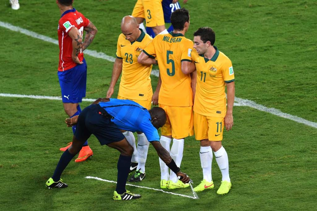 Referee Noumandiez Doue sprays a temporary line for the Socceroos' wall to stay behind during a free kick.