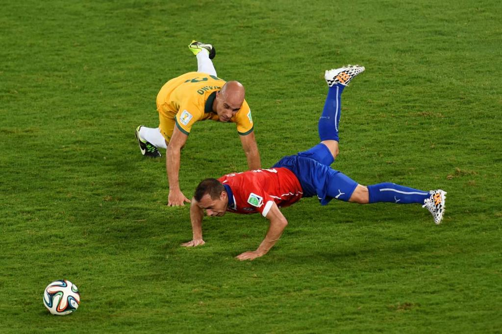 Australia's Mark Bresciano and Chile's Marcelo Diaz collide in Cuiaba.