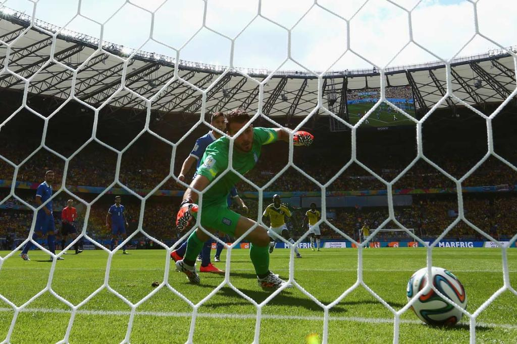 Greece goalkeeper Orestis Karnezis watches as Colombia's first goal rolls across the line.