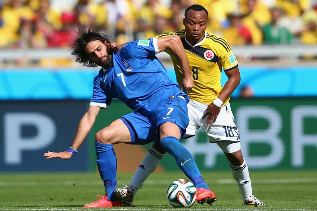 Greece's Giorgos Samaras holds the ball as Colombia's Juan Camilo Zuniga hassles him.