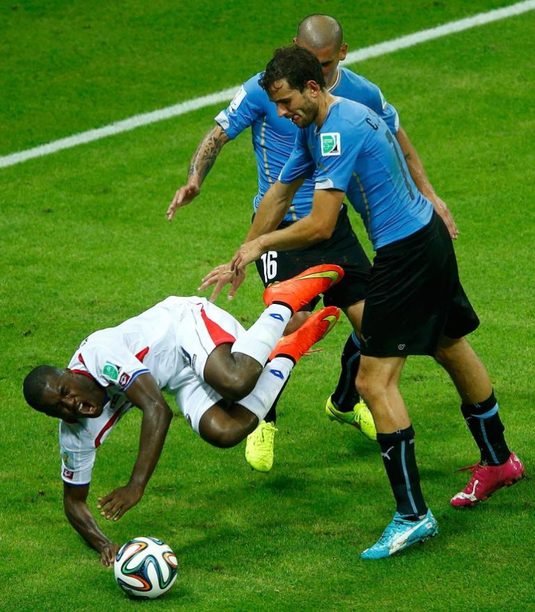 Costa Rica's Joel Campbell is fouled by Uruguay's Maximiliano Pereira, who was issued a red card for the foul.