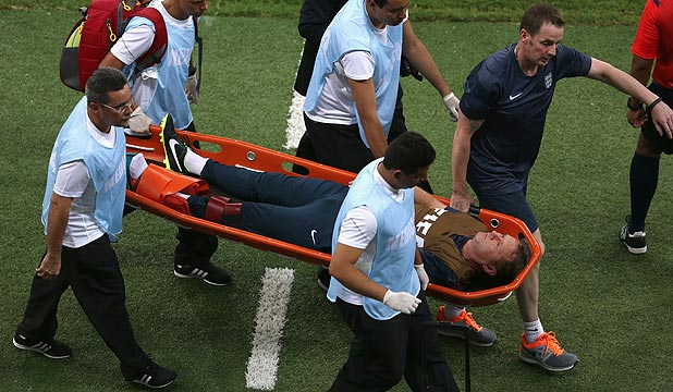 IRONIC: England trainer Gary Lewin is stretchered off the field after injuring his leg celebrating his team's first and only goal against Italy.