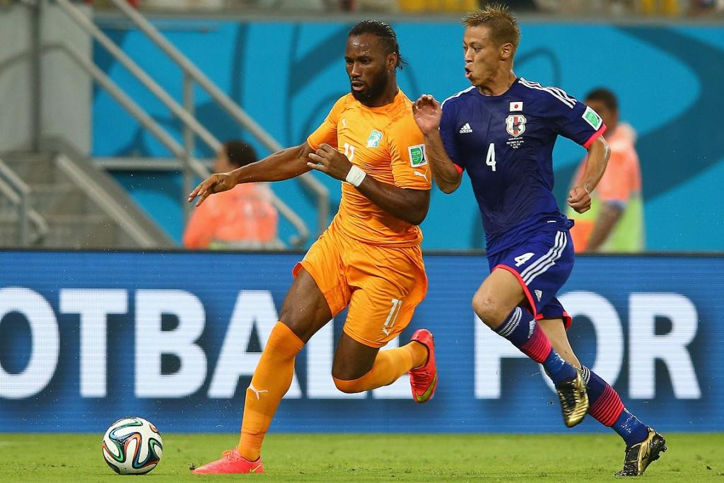 Didier Drogba of the Ivory Coast controls the ball against Keisuke Honda of Japan during their Group C match.