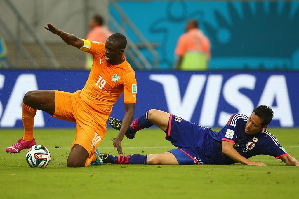 Maya Yoshida of Japan tackles Yaya Toure of the Ivory Coast.