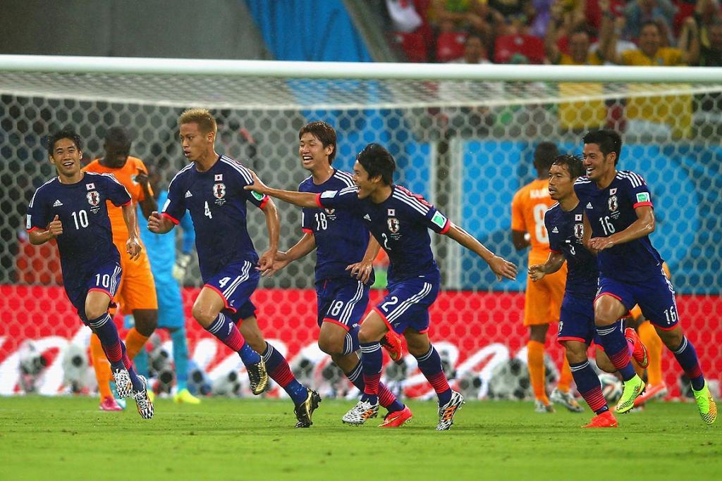 Keisuke Honda of Japan (2nd L) celebrates scoring the team's first goal with teammates during the 2014 FIFA World Cup Brazil Group C match between the Ivory Coast and Japan