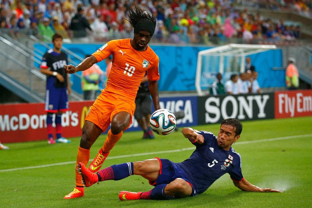 Yuto Nagatomo of Japan tackles Gervinho of the Ivory Coast during the 2014 FIFA World Cup Brazil Group C match between the Ivory Coast and Japan