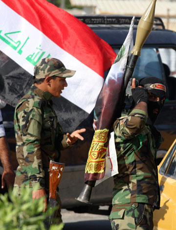 Volunteers who have joined the Iraqi Army to fight against predominantly Sunni militants carry weapons during a parade in the streets in Baghdad's Sadr city on Saturday.