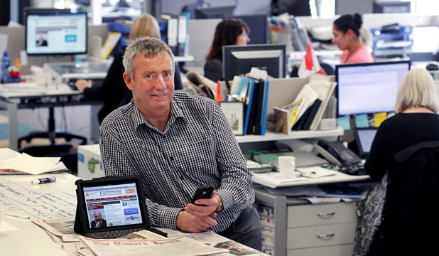 MULTIPLE OUTLETS: Editor Peter O'Neill in the newsroom of today, where stories go not just to the traditional newspaper but also  online, the latter of which are accessed via desktop computers and increasingly through tablets and smart phones.