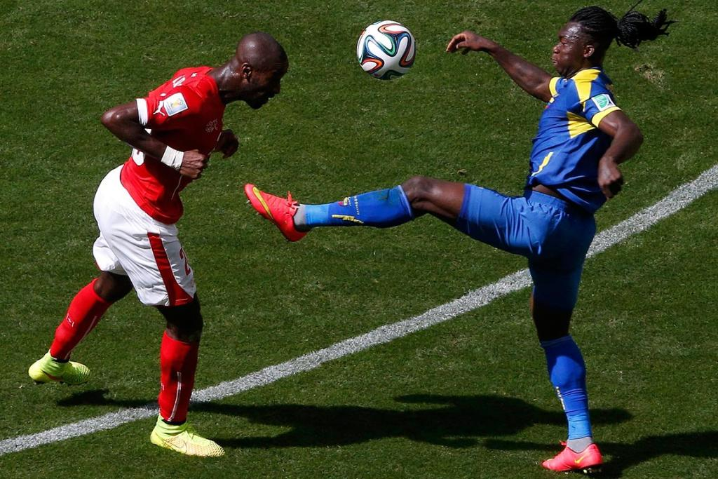 Switzerland's Johan Djourou fights for the ball with Ecuador's Felipe Caicedo.