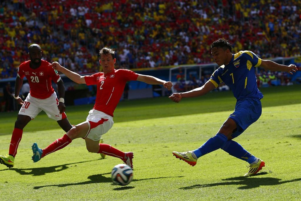 Switzerland's Johan Djourou and Stephan Lichtsteinerf ight for the ball with Ecuador's Jefferson Montero.