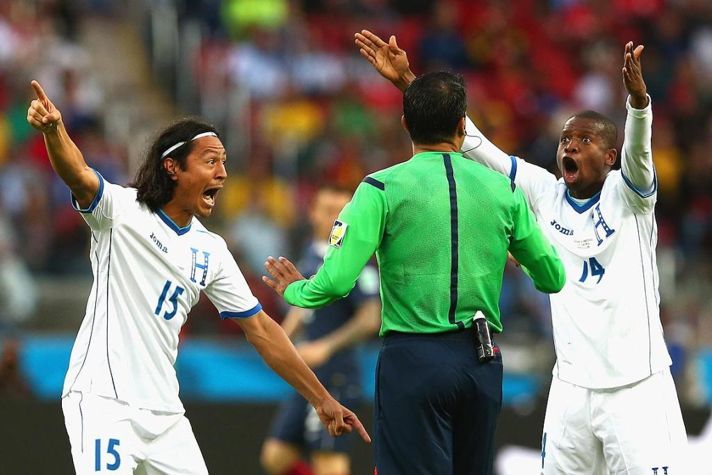 Roger Espinoza and Oscar Boniek Garcia of Honduras protest France's second goal.