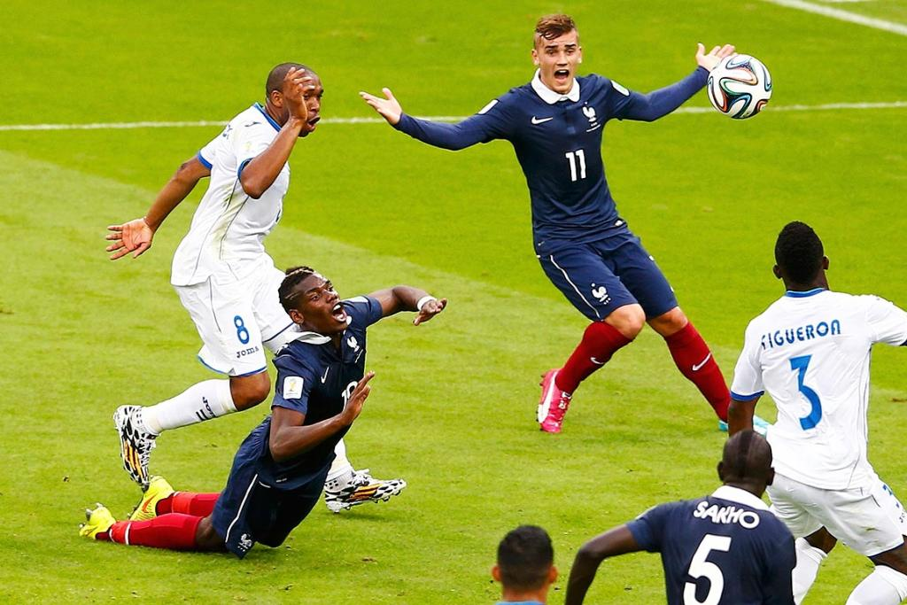 France's Paul Pogba falls near teammate Antoine Griezmann after being fouled by Wilson Palacios of Honduras.