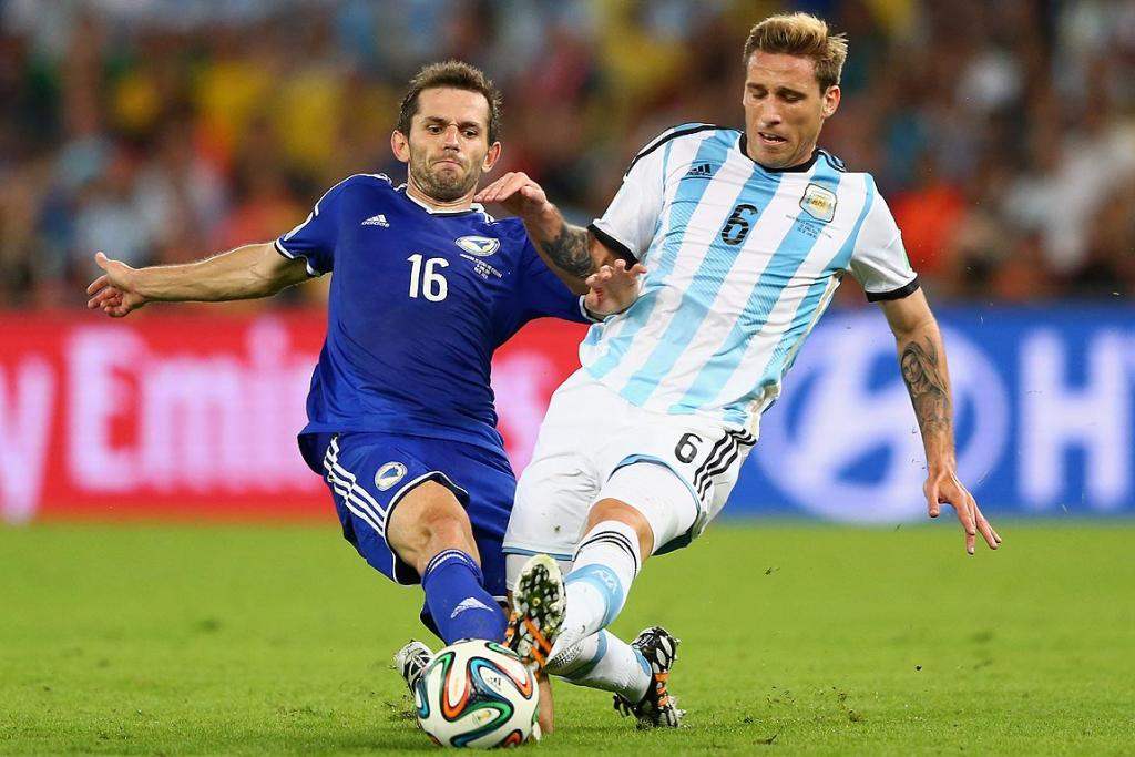 Senad Lulic of Bosnia and Herzegovina challenges Lucas Biglia of Argentina.