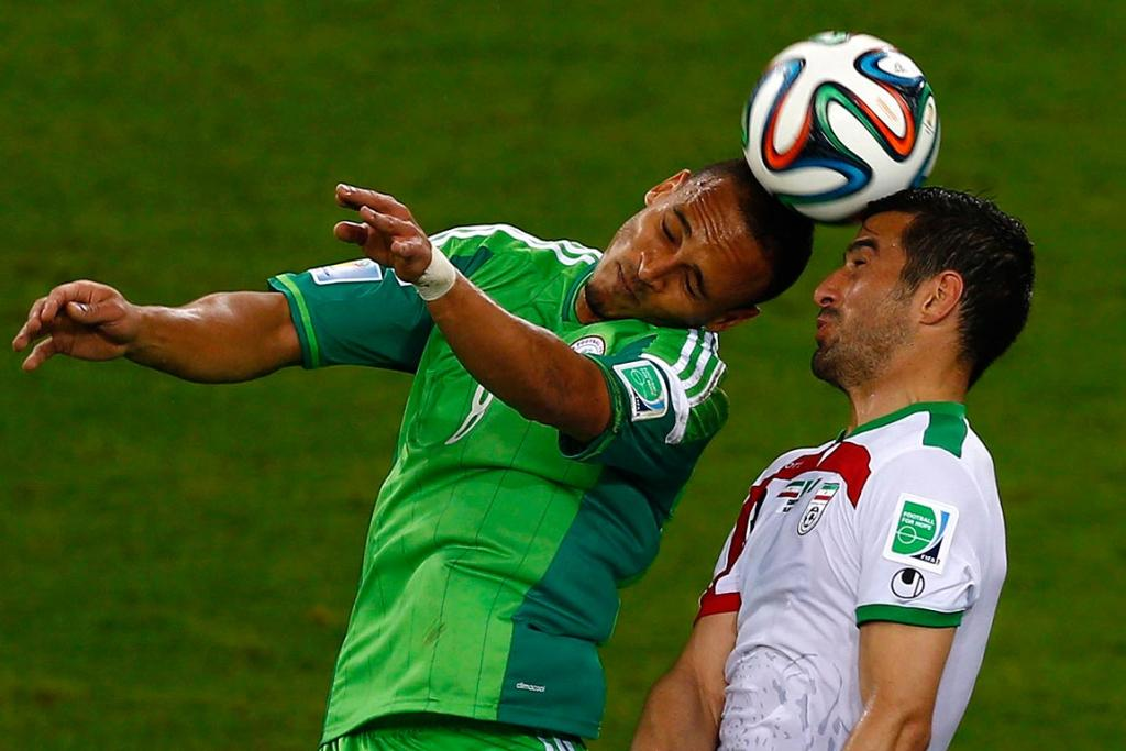 Iran's Ehsan Hajsafi and Nigeria's Peter Odemwingie jump for the ball.