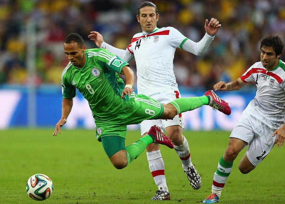 Peter Odemwingie of Nigeria falls after a challenge by Andranik Teymourian of Iran.