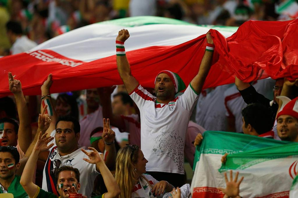 Supporters hold up the Iran flag.