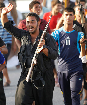READY TO FIGHT: Volunteers, who have joined the Iraqi Army to fight against the radical Islamic State of Iraq and the Levant, carry weapons during a parade in eastern Baghdad on Monday.