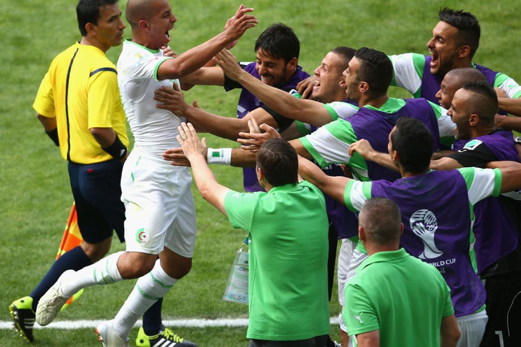 Sofiane Feghouli of Algeria celebrates with his teammates after scoring his team's first goal from a penalty kick against Belgium at Estadio Mineirao in Belo Horizonte, Brazil.