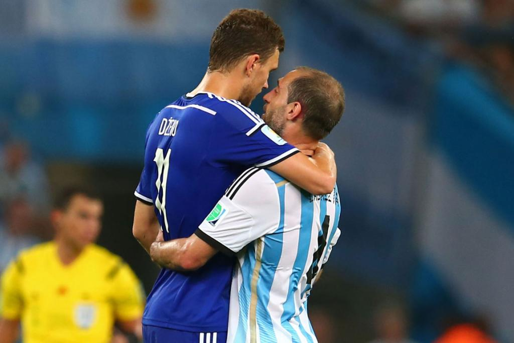 Edin Dzeko of Bosnia and Herzegovina (L) and Pablo Zabaleta of Argentina hug and whisper sweet nothings after the match between their two teams.