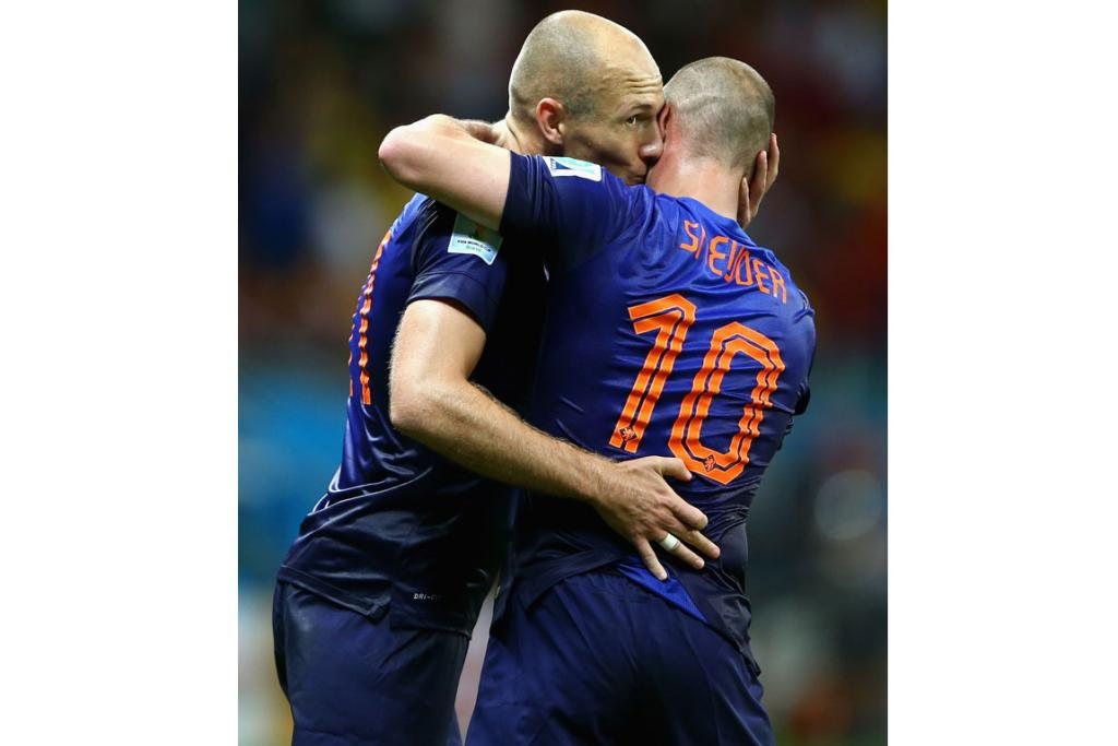Arjen Robben of the Netherlands gives teammate Wesley Sneijder a peck during their match against Spain.