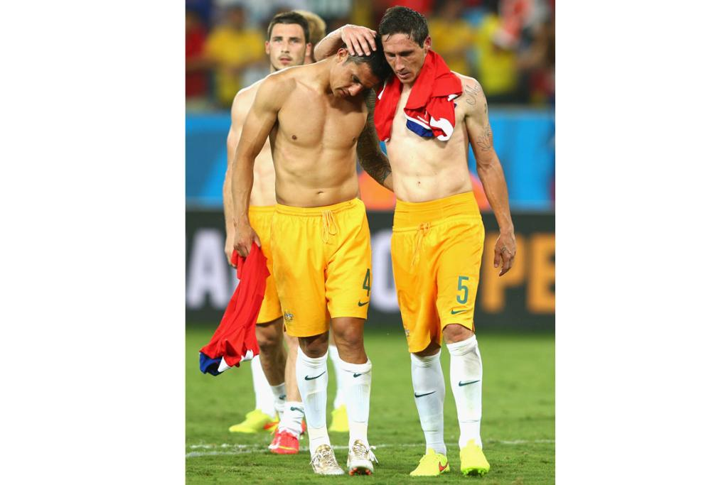 Tim Cahill (L) and Mark Milligan of Australia consle one another after being defeated by Chile 3-1.