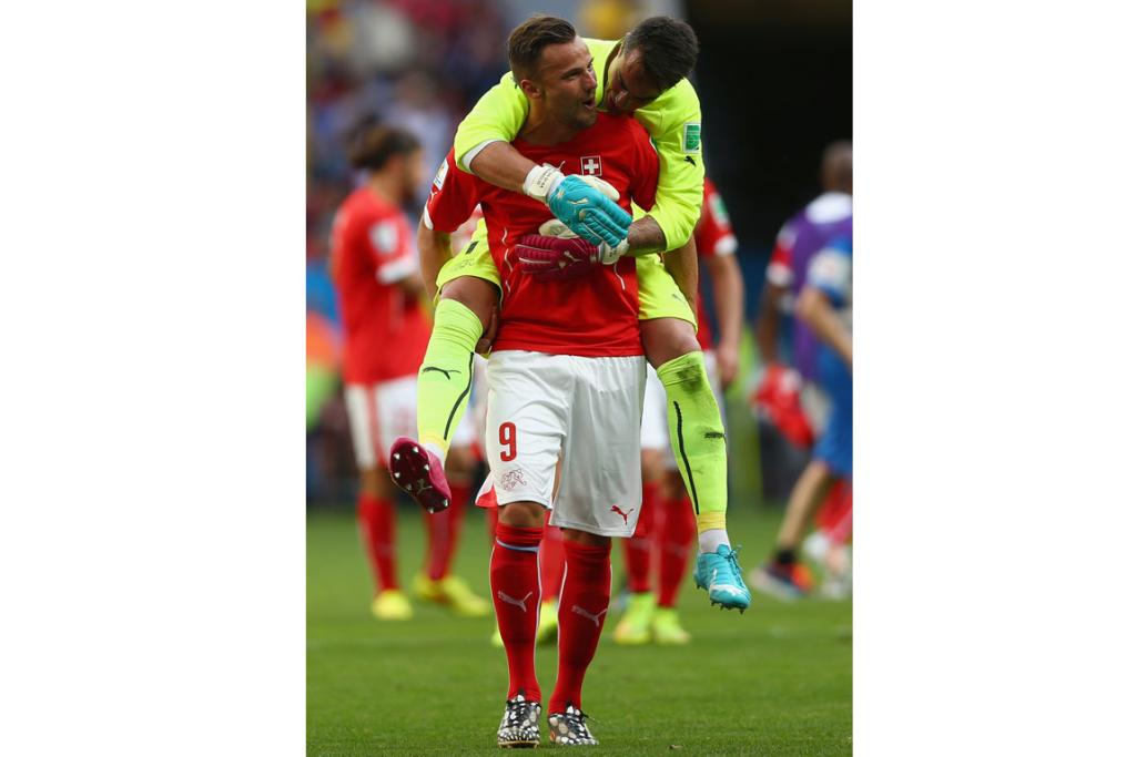 Haris Seferovic of Switzerland (front) enjoys a touchy-feely celebration with goalkeeper Diego Benaglio after defeating Ecuador 2-1.