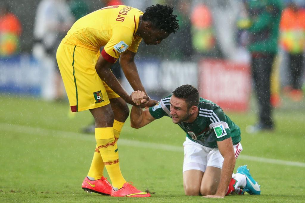 Benjamin Moukandjo of Cameroon tries to help Miguel Layun of Mexico to his feet - oh bless.