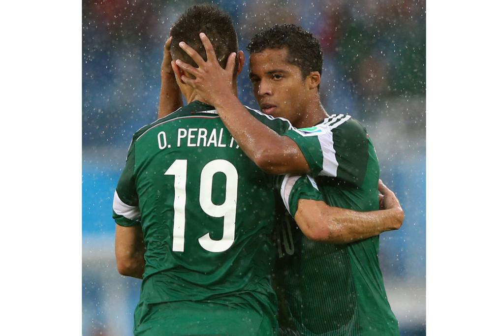 Oribe Peralta of Mexico (L) gives teammate Giovani dos Santos a once over while celebrating a goal during their match against Cameroon.