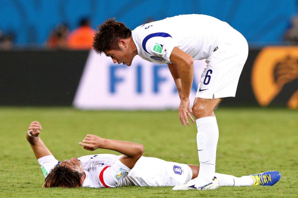 Hwang Seok-Ho of South Korea consoles Kim Young-Gwon during their World Cup Group H match against Russia at Arena Pantanal in Cuiaba, Brazil.