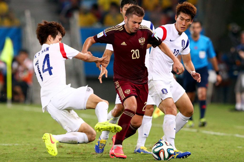 Victor Fayzulin of Russia controls the ball against Han Kook-Young (left) and Lee Yong of South Korea during their Group H match at Arena Pantanal in Cuiaba, Brazil.