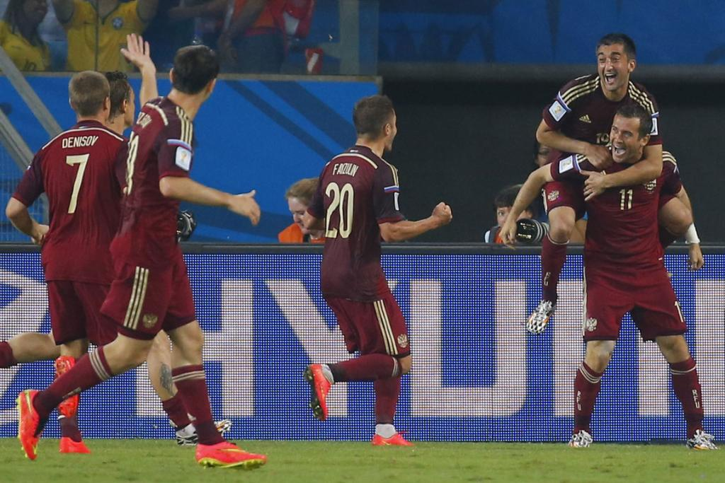Russia's Alexander Kerzhakov (top right) celebrates his goal with teammates during their 1-1 draw with South Korea at the World Cup.