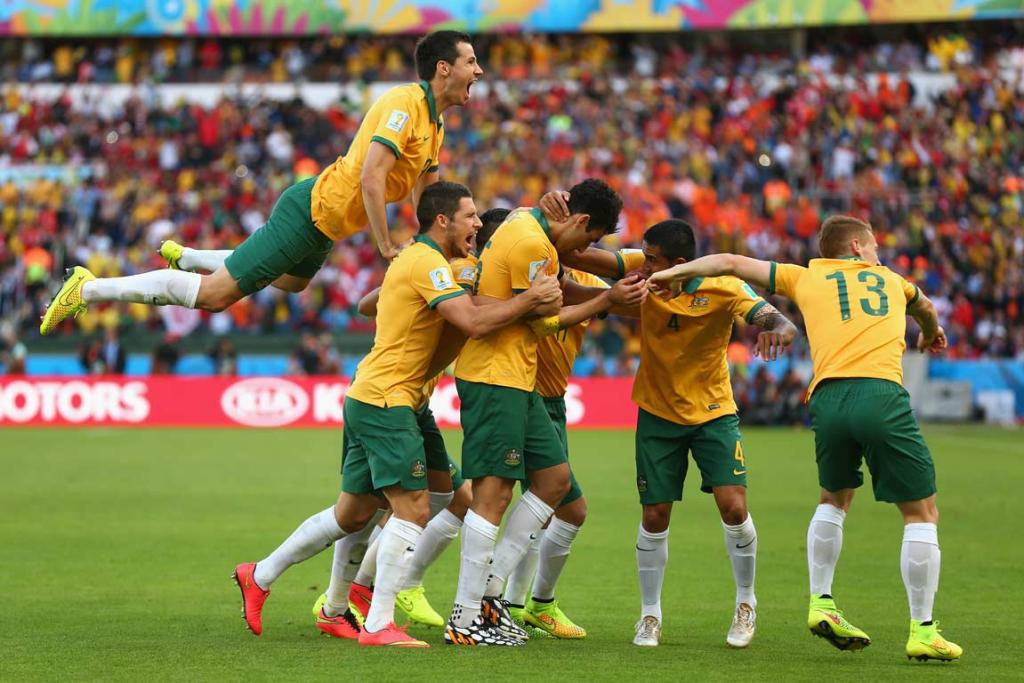 Australian captain Mile Jedinak is somewhere under the pile after converting his spot kick for a 2-1 lead.
