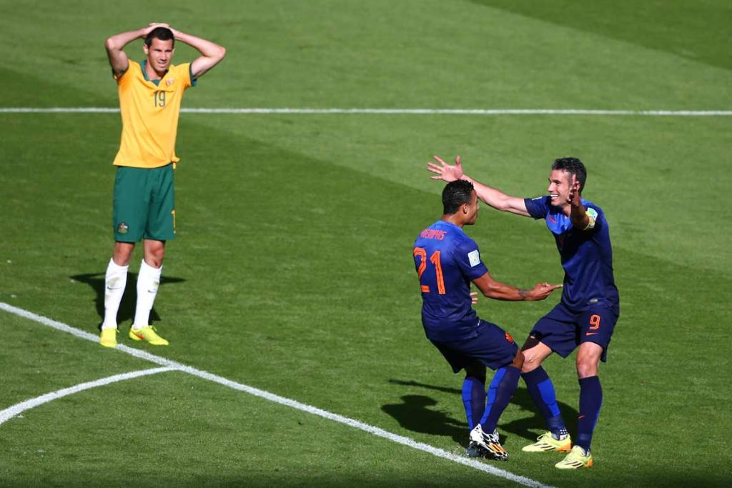 Australia's Ryan McGowan looks on in disappointment as Memphis Depay celebrates his match-winning goal with Robin van Persie.