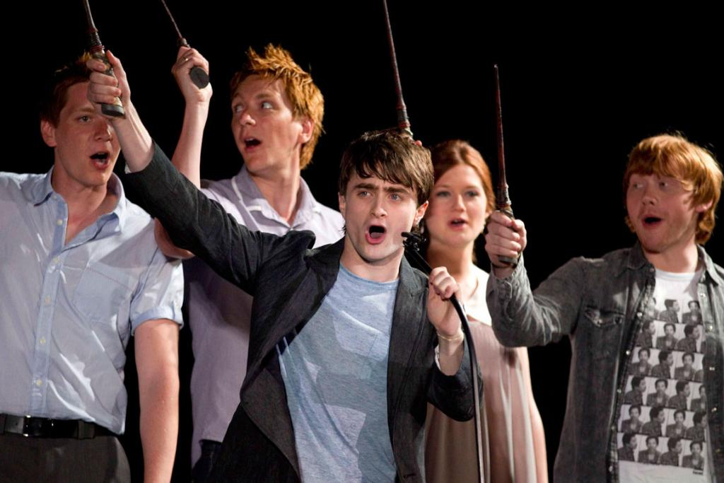 Daniel Radcliffe (C) and members of the cast of Harry Potter wave their wands at The Wizarding World of Harry Potter at Universal Studio Resort.