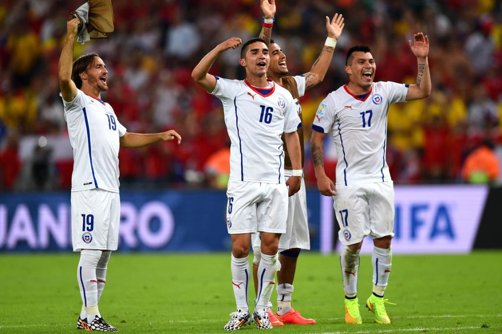 Jose Pedro Fuenzalida, Felipe Gutierrez and Gary Medel of Chile celebrate a 2-0 victory over Spain in their Group B match at Maracana in Rio de Janeiro, Brazil.