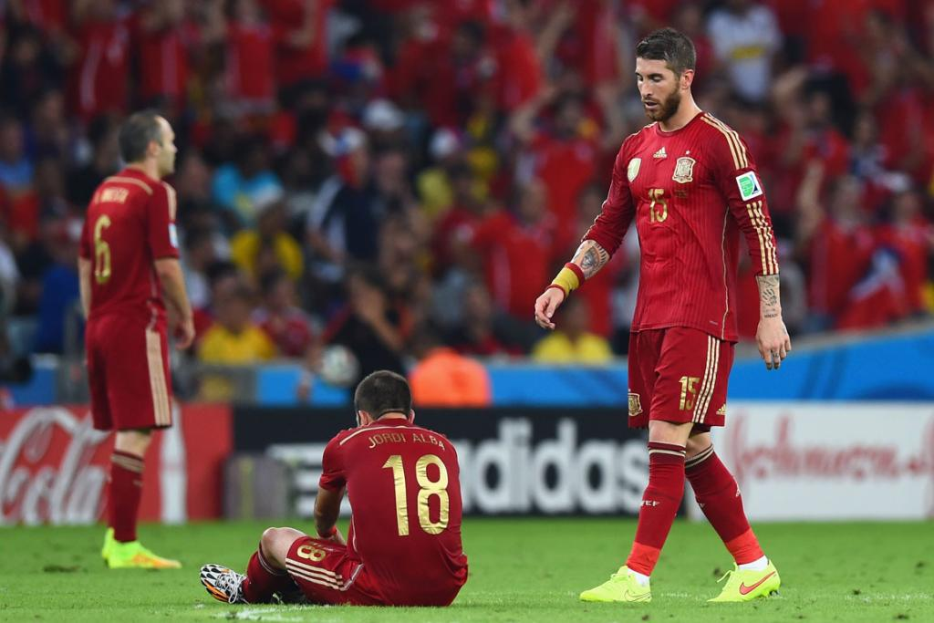 Sergio Ramos of Spain looks on as teammate Jordi Alba fixes his boot during the World Cup Group B match at Maracana in Rio de Janeiro, Brazil.