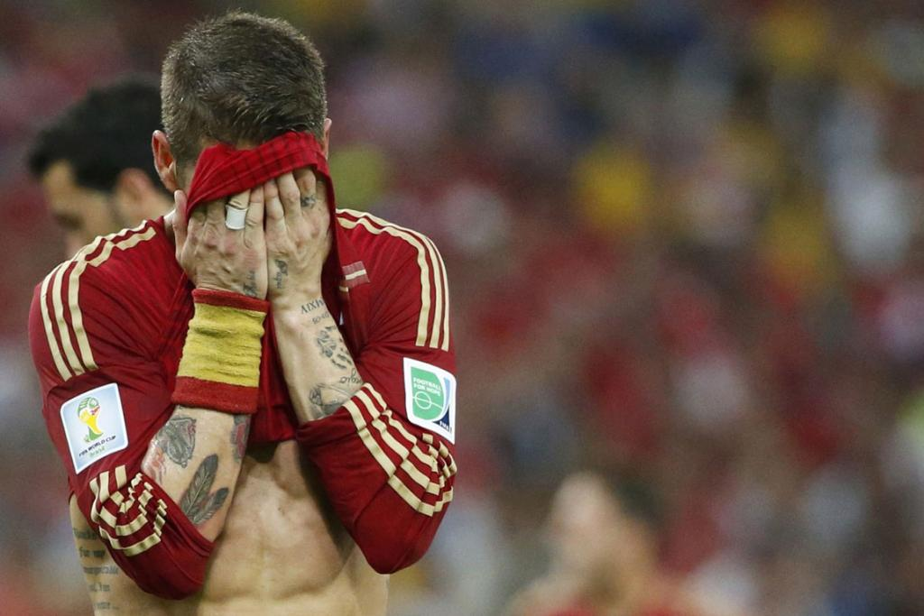 Spain's Sergio Ramos tries to hide his disappointment after a shock 2-0 loss to Chile during their World Cup Group B football match at the Maracana stadium in Rio de Janeiro, Brazil.