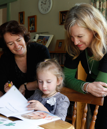 FUN AND EASY:  Carolyn Sygrove, left, and Lisa Caron show Tessa Bagnall their new book that uses technology to help young children  learn another language