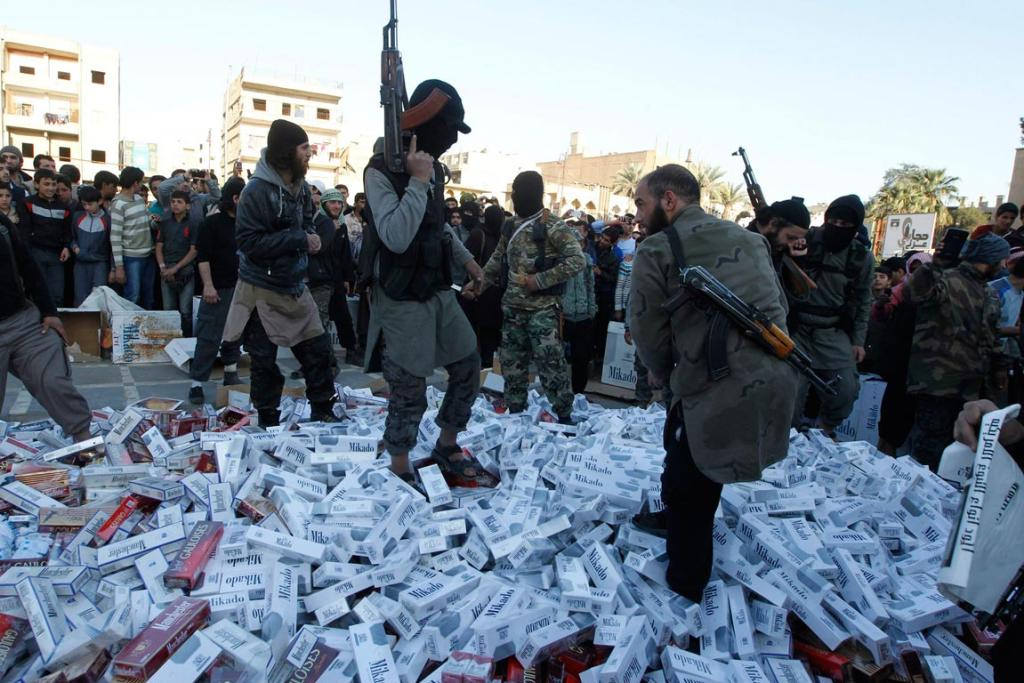 ISIL imposes harsh laws on areas they control, including restrictions on women, association, speech, and a ban of alcohol and cigarettes. Their punishments include cutting off hands and beheadings. Fighters are shown here stomping on confiscated cigarettes.