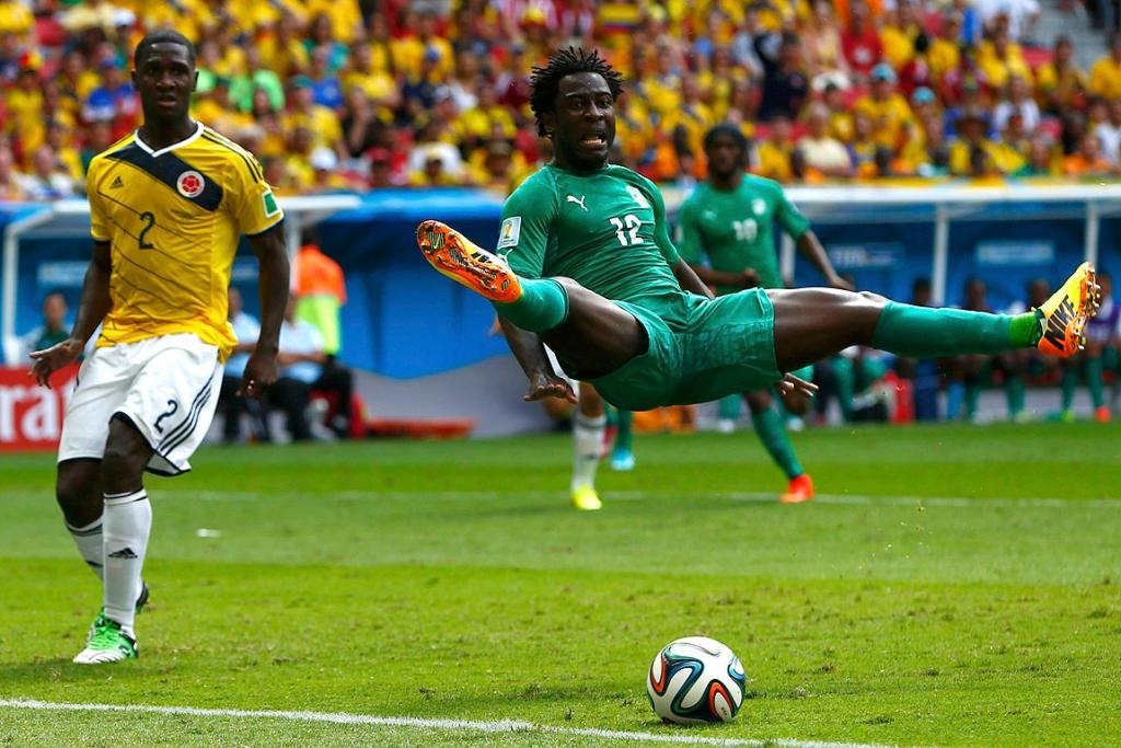 Colombia's Cristian Zapata watches as Ivory Coast's Wilfried Bony jumps.